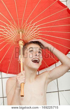 Boys Standing In Shower Under Umbrella