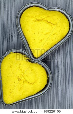 Top view of heart shaped corn bread cake on grey background