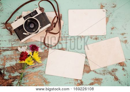 Retro camera and empty old paper photo album on wood table with flowers border design - concept of remembrance and nostalgia in spring. vintage style