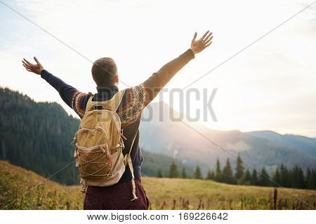 Rearview of a man in hiking gear with his arms raised to the sky embracing the sunrise while trekking in the wilderness