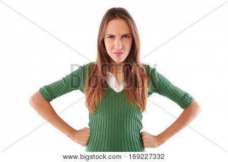 Close-up of a young girl, her face shows a disgusting reaction. Holding hands on hips. Wearing green sweater, standing over white background