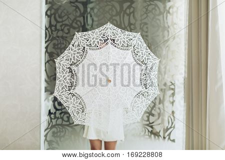 Bride in white dress and with lace umbrella in hands. Studio photo.