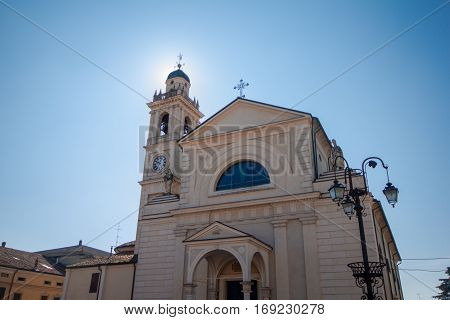The church of Brescello with the sun filtering through the bell tower.