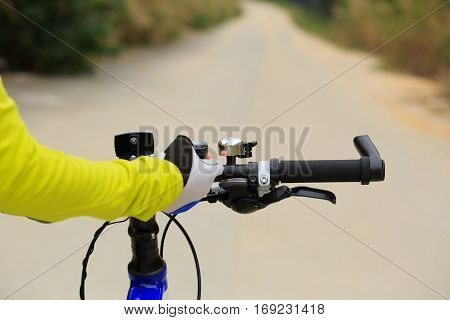 cyclist setting stopwatch before riding mountain bike on forest trail