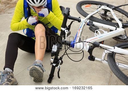 female cyclist getting injured while falling from mountain bike on road