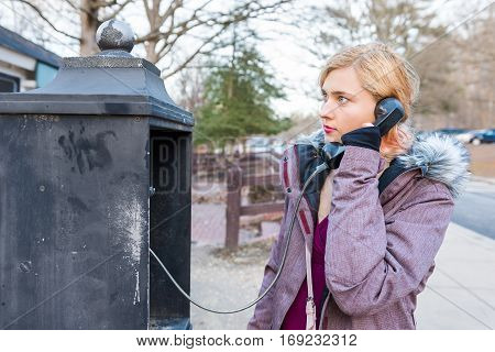 Young woman calling in phonebooth in winter