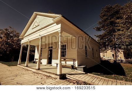 Toronto, Ontario, Canada, Black Creek Pioneer Village park, Oct. 10, 2016, amazing view of old vintage classic architecture town hall in outdoor park on dark dramatic blue sky background
