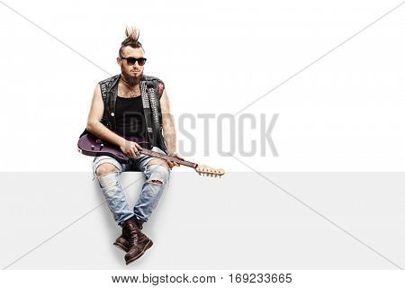 Young punker with an electric guitar sitting on a panel isolated on white background