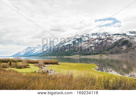 Grand Teton mountains with lake and dark stormy cloudy overcast sky in national park
