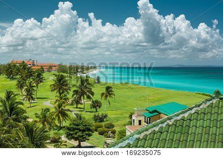 stunning  amazing, inviting wide open view of tropical natural background, against tranquil azure ocean with magic fluffy clouds on deep dark blue sky