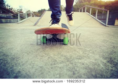 young skateboarder legs riding skateboard at skatepark