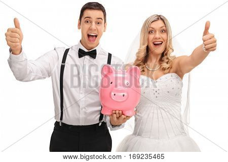 Overjoyed newlywed couple holding a piggybank and giving thumbs up isolated on white background