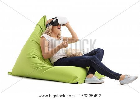 Amazed woman seated on a beanbag using a VR headset and eating popcorn isolated on white background