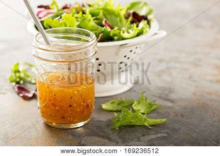 Italian vinaigrette dressing in a mason jar with fresh vegetables on the table