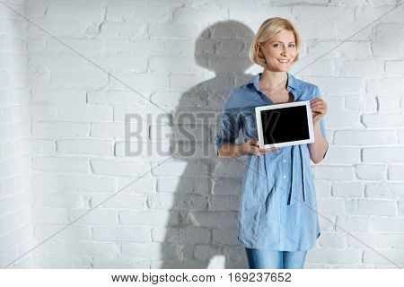 Happy woman holding tablet computer with blank screen, smiling, looking at camera.