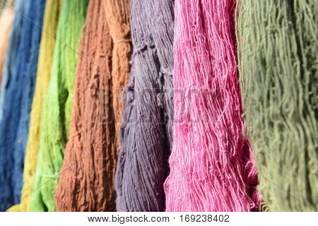 The raw organic cotton yarn in tray with the colorful thread.The yellow organic handmade cotton