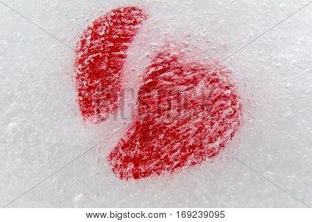 Red broken heart frozen in ice, center