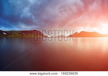 Lake coast with mountain reflection at the sunrise, Iceland. treking in Iceland. Travel concept.