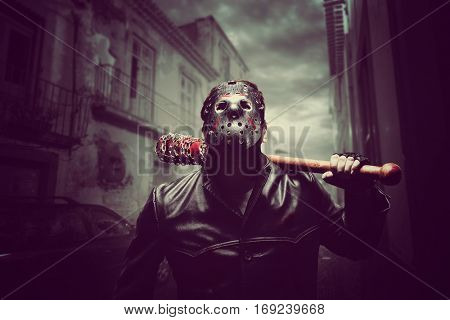 Psycho man in hockey mask with bloody baseball bat