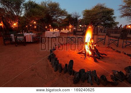 Nighttime campfire and decorated tables for outdoor safari catering