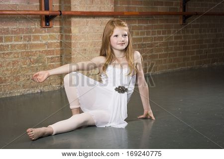 Beautiful young and talented dancer posing at a dance studio. Full length photo of a cute ballerina with copy space