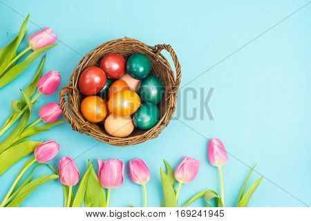 Top view of Easte still life with basket of eggs and tulips with copy space