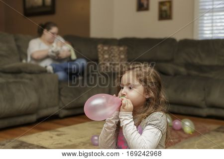 little girl blowing up a balloon in her living room floor as her mother sits holing a baby behind her