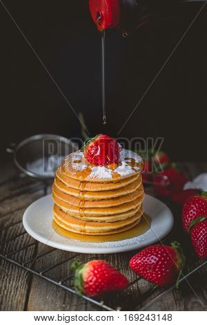 Breakfast Time with Fresh Strawberry on Stack of Pancake Pouring over by Maple Syrup