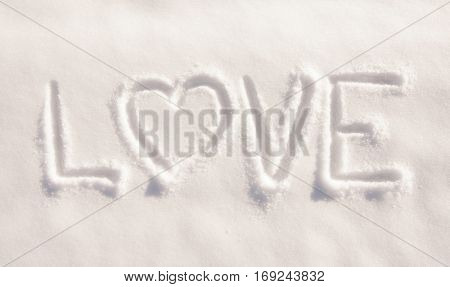 Word love with a heart, written in fresh powdery snow - concept of loving winter weather
