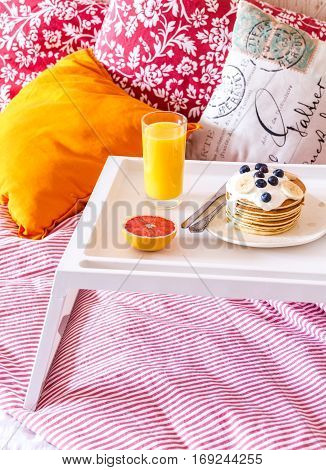 concept of breakfast in bed on tray with juice.