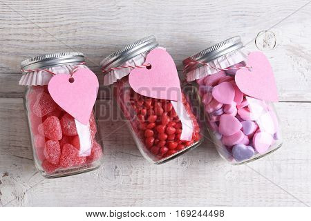 Canning jars laying on their sides filled with candy hearts and for Valentine's Day on a rustic wood table. The jars have blank heart shaped gift tags hanging from the neck.