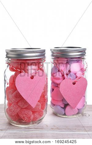 Two canning jars filled with Valentines Day candy hearts. Vertical format with copy space.
