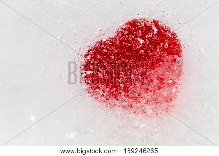 Red heart frozen in ice on side Valentine's Day background