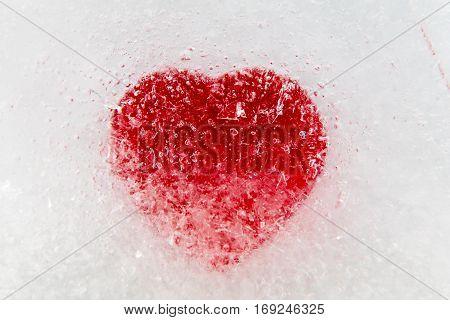 Red heart frozen in ice center, macro, selective focus