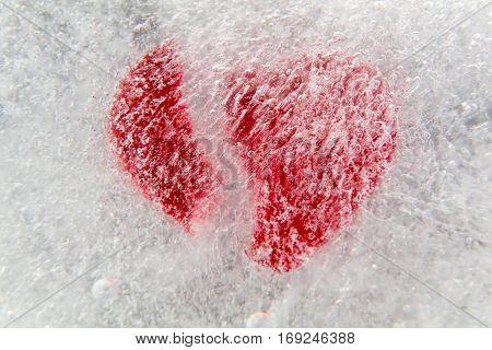 Red broken heart frozen in ice, macro, selective focus, for Valentine's Day