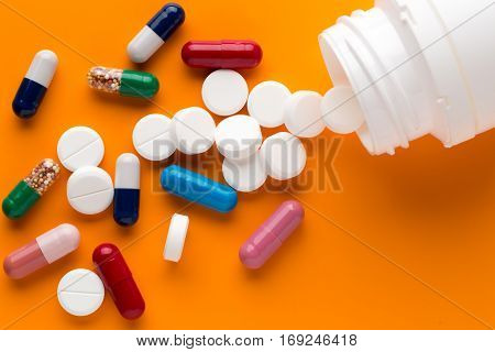 Different multicolored pills and medicine capsules on orange background