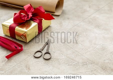 wrapping gifts in box for holiday on stone background.