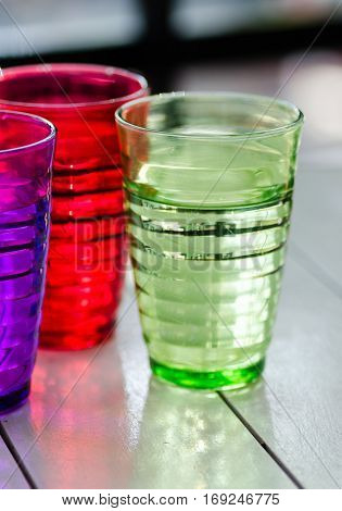 Colorful glasses on wooden table as stylish background.