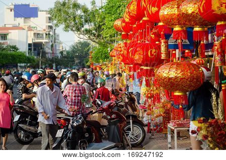 NHA TRANG VIETNAM - JANUARY 27 2017: A lot of peoble buying decorations for lunar New Year in a central street of Nha Trang. Lunar New Year - Tet is the most important holiday in Vietnam