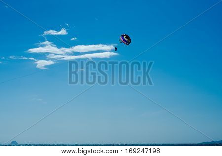 Bright parasailing couple against bright blue sky.
