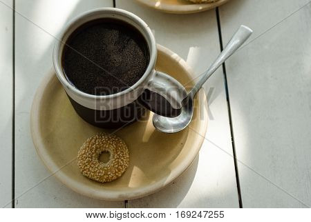 Hot sweet coffee with cinnamon powder in clay cup.