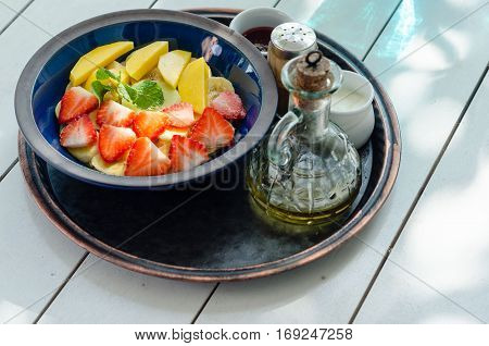 Clay bowl with fruit salad. Yogurt and honey in glass bottle