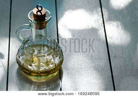 Small glass jar with oil on white wooden table. Space for text.