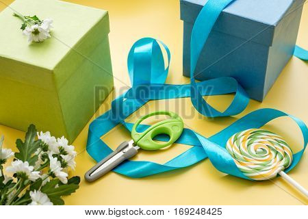 wrapping gifts in box for holiday on yellow background.