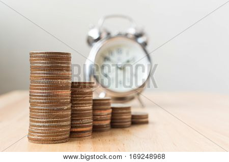 Concept business finance save money Coins stack on wood table with blurred alarm clock