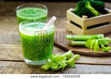 Green vegetable smoothie in glass at wooden background.