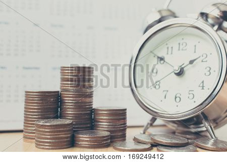 Concept business finance save money Coins stack on wood table with calendar and alarm clock