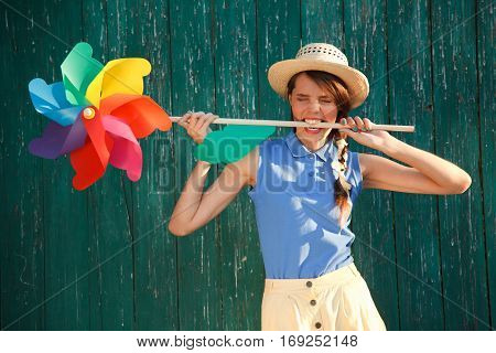 Young happy funny (vintage) dressed woman with colorful weather vane in her teeth. Old green fence on the background. Picture ideal for illustating woman magazines.