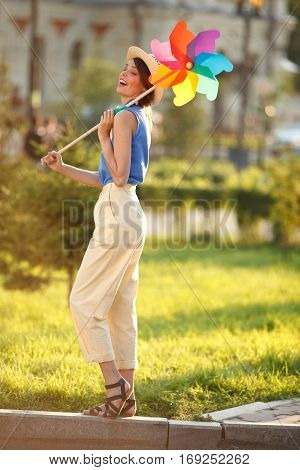 Young happy funny (vintage) dressed woman with colorful weather vanelooking like flower Picture ideal for illustating woman magazines.