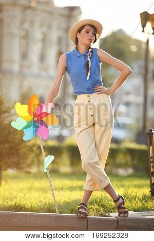 Young happy funny (vintage) dressed woman on the street with colorful weather vanelooking like flower Picture ideal for illustating woman magazines.